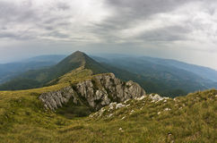Rocks and cliffs under dark clouds trekking path at Suva Planina mountain Royalty Free Stock Photography