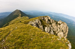 Rocks and cliffs under dark clouds trekking path at Suva Planina mountain Royalty Free Stock Image