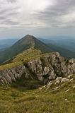 Rocks and cliffs under dark clouds trekking path at Suva Planina mountain Royalty Free Stock Images