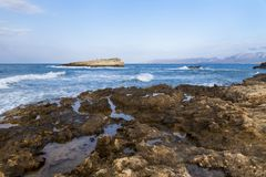 The rocks are in contact with the sea. Rocky beach, sharp rocks touching the sea, Greece island of Crete royalty free stock images