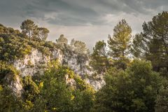 Rocks covered with grass, trees against a gray sky with clouds. Horizontal Royalty Free Stock Image