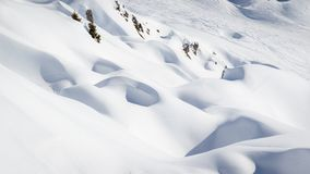 Rocks covered by pristine snow in mountains. Rocks covered by pristine powder snow in French Alps mountains royalty free stock photos