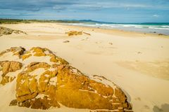 Rocks covered by sand on the beach in Mallacoota Stock Images
