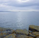 Rocks pointing out to sea. Rocks covered in yellow lychen pointing out towards the sea on a sunny day Stock Photos