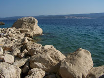 Rocks on the croatian beach. Wild rocky beach in Croatia with a beautiful blue sea and mountains in the background Stock Photography