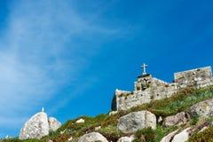 Rocks, cross and seagull in Baiona Stock Photos