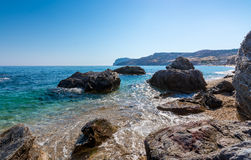 Rocks in crystal clear turquise waters of paliochori beach in Mi Royalty Free Stock Images