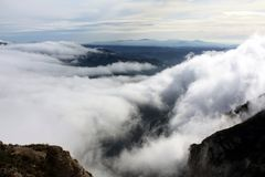 Rocks in dense clouds. Panoramic view of dense clouds and rocks from huge height, in a pre-dawn haze stock photography