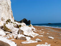 Rocks on a Dorset beach. Large limestone rocks fallen on the beach reflecting the sunlight with Durdle Door in the distance Royalty Free Stock Photography