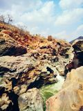 Rocks drilled by water and water flow. The photo was took at makadhatu, dangerous place to visit, the kaveri river flows between the rocks royalty free stock photography