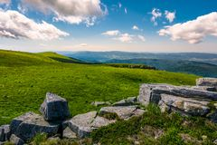 Rocks on the edge of grassy meadow on hillside. Lovely landscapes of Runa mountain Stock Images