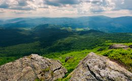 Rocks on the edge of a  mountain. Location Pikui mountain. Runa mountain in the far distance. Beautiful summer landscape of Carpathian mountains on a cloudy Stock Images