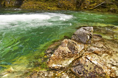 Rocks with emerald green water. Rocky landscape with emerald green water and waterfall royalty free stock photo