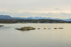 Rocks in the evening water. Beatiful rocks in the foreground, horizon with town and mountains in the background Royalty Free Stock Images