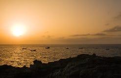 Rocks and fisherboats at sunset, El Hierro. Sunset at Las Puntas, El Hierro, Canary Islands, Spain stock image