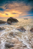 Rocks and A Fishing Boat at sunset Stock Photo