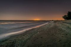 Rocks in a flat sea at night stock photography