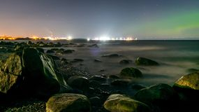 Rocks in a flat sea at night. northern lights. aurora borealis stock images