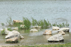 Rocks in flooded quarry. Group of lonely stones in flooded quarry. This photo has been taken near Mikulov, Czech Republic Stock Photography