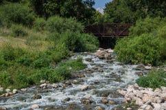 Footbridge over the San Antonio River. A footbridge over the San Antonio river, as it flows over rocks in Espada Park, San Antonio, Texas Stock Photography