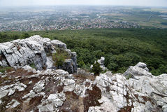 Rocks in the forest and the city in the background Stock Photography