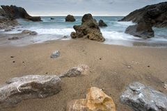 Rocks getting dark in the beach of Miengo Stock Images