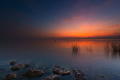 Rocks and grass in lake at red orange sunset Royalty Free Stock Photo