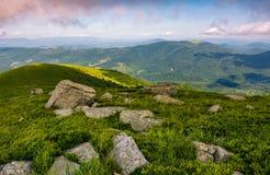 Rocks on grassy hillside of Carpathian mountains. Landscape with rocks on grassy alpine hillside of Carpathian mountain ridge. Gorgeous view of Polonina on fine Royalty Free Stock Photography