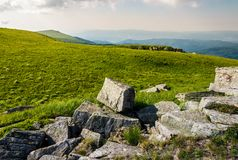 Rocks on grassy meadow on top of a hill. Beautiful summer scenery in mountains Royalty Free Stock Photography