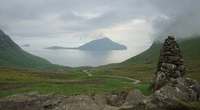 rocks and green field on the mountain with view of the ocean, Torshaven, faroes island