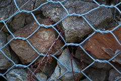 Rocks held by fence Royalty Free Stock Photos