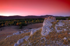 Rocks of high mountains. With red sky Stock Image