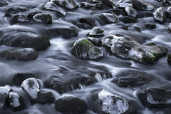Rocks with ice in streaming water Stock Photos
