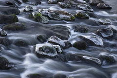 Rocks with ice in streaming water Stock Photo