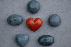 Rocks inristade med ordförälskelse, fred, kurage, hopp, glädje som omger en röd hjärta Royaltyfria Foton