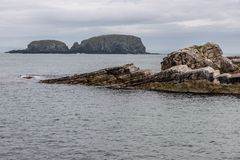 Rocks and island in Ballintoy Harbour. Moyle, Northern Ireland, UK royalty free stock images