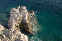 Rocks jutting out into sea. Vertical view of rocks jutting out into the sea Royalty Free Stock Photography