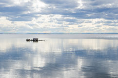 Rocks in lake with clouds mirroring in the water Royalty Free Stock Photo