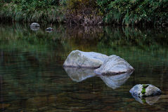Rocks in lake or river. Scenic view of rocks reflecting on lake or river Royalty Free Stock Image