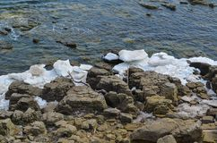 Rocks located near the sea, in winter ice floes break about them. beautiful view royalty free stock photo