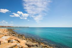 Rocks of the marina and clear blue water at the Mediterranean Sea on a summer day royalty free stock photos