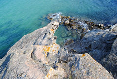 Rocks merging into the sea Royalty Free Stock Image