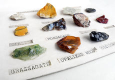 Rocks minerals collection hobby. An image showing an antique colorful rock collection.  Displayed on white cardboard and labelled rock samples include grass Royalty Free Stock Photo