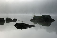 Rocks and Mist. Rocks Shrouded in Early Morning Mist on a Lake in Northern Ontario, Canada Royalty Free Stock Photography