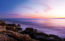 Rocks in the misty sea in sunset Royalty Free Stock Photo