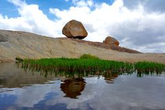 Rocks on mountain with reflection. On the mountains, there are rocks with beautiful reflection of them and the bright clouds enhances the picture making it look Stock Images