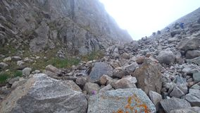 Among the rocks and mountains grow purple flowers. On the rocks grow flowers. A group of tourists climbs the mountains. The rise in the mist stock footage