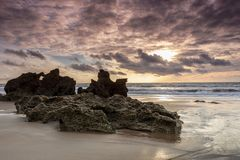 Rocks on the muddy beach in Cadiz at sunset royalty free stock photography