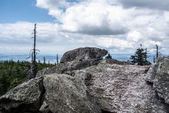 Rocks named Hranicni skaly on Kralicky Sneznik mountains on czech - polish borders. With hills on the background and blue sky with clouds Stock Photos