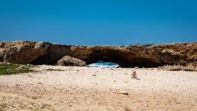 Rocks near a Natural bridge formation in Aruba`s north coast. Rocks stacked on a deserted beach near a natural bridge formation on the North coast of Aruba stock photos